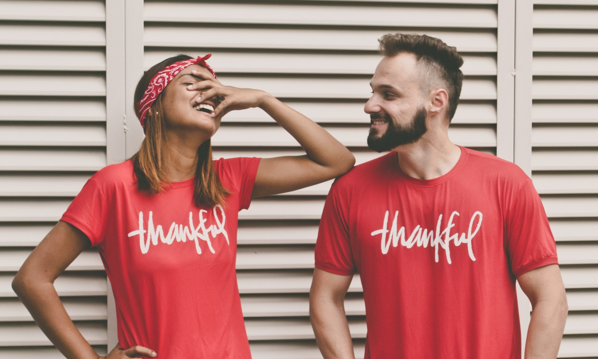 Man and woman smiling and being thankful while standing in front of louver door