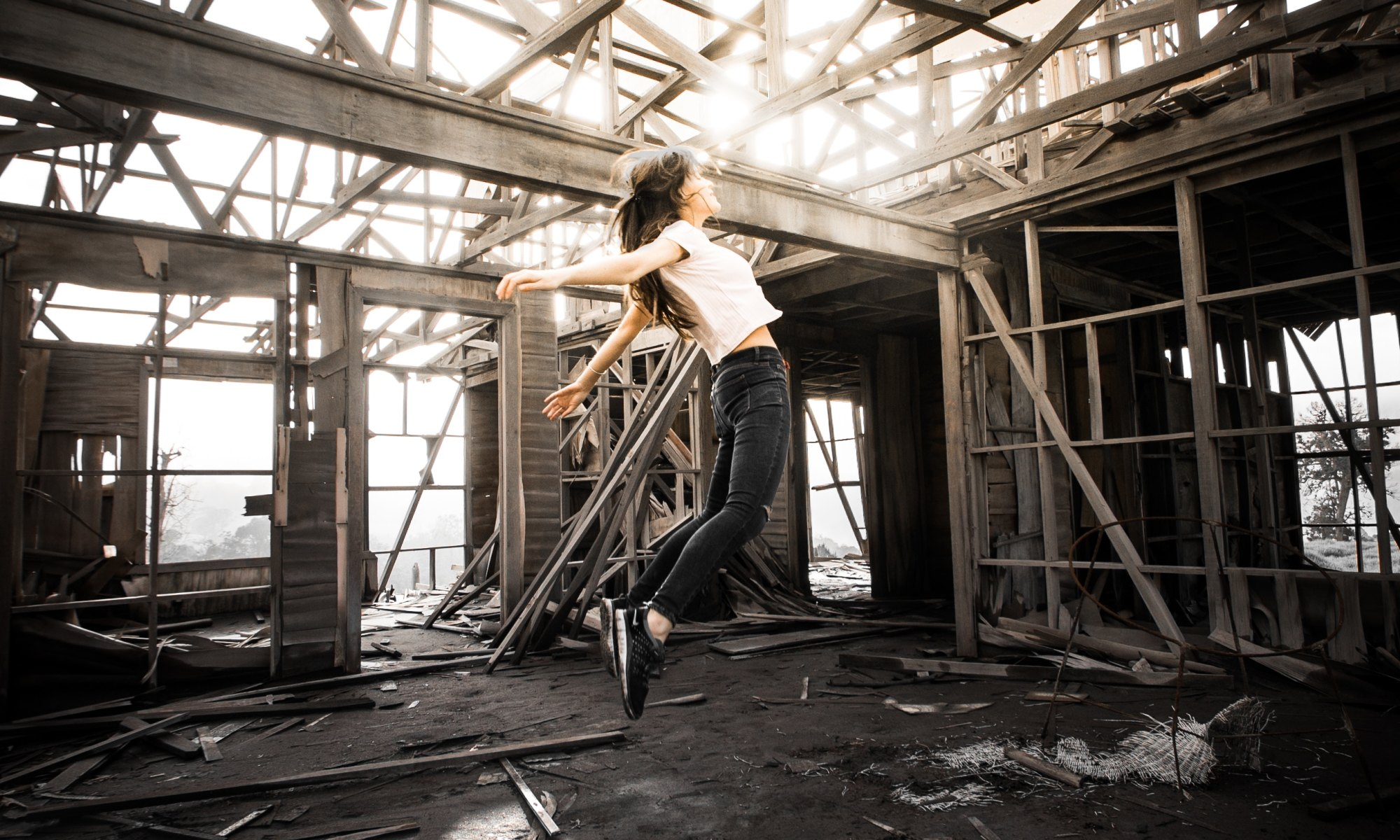Impulsive woman jumping in a burned down house
