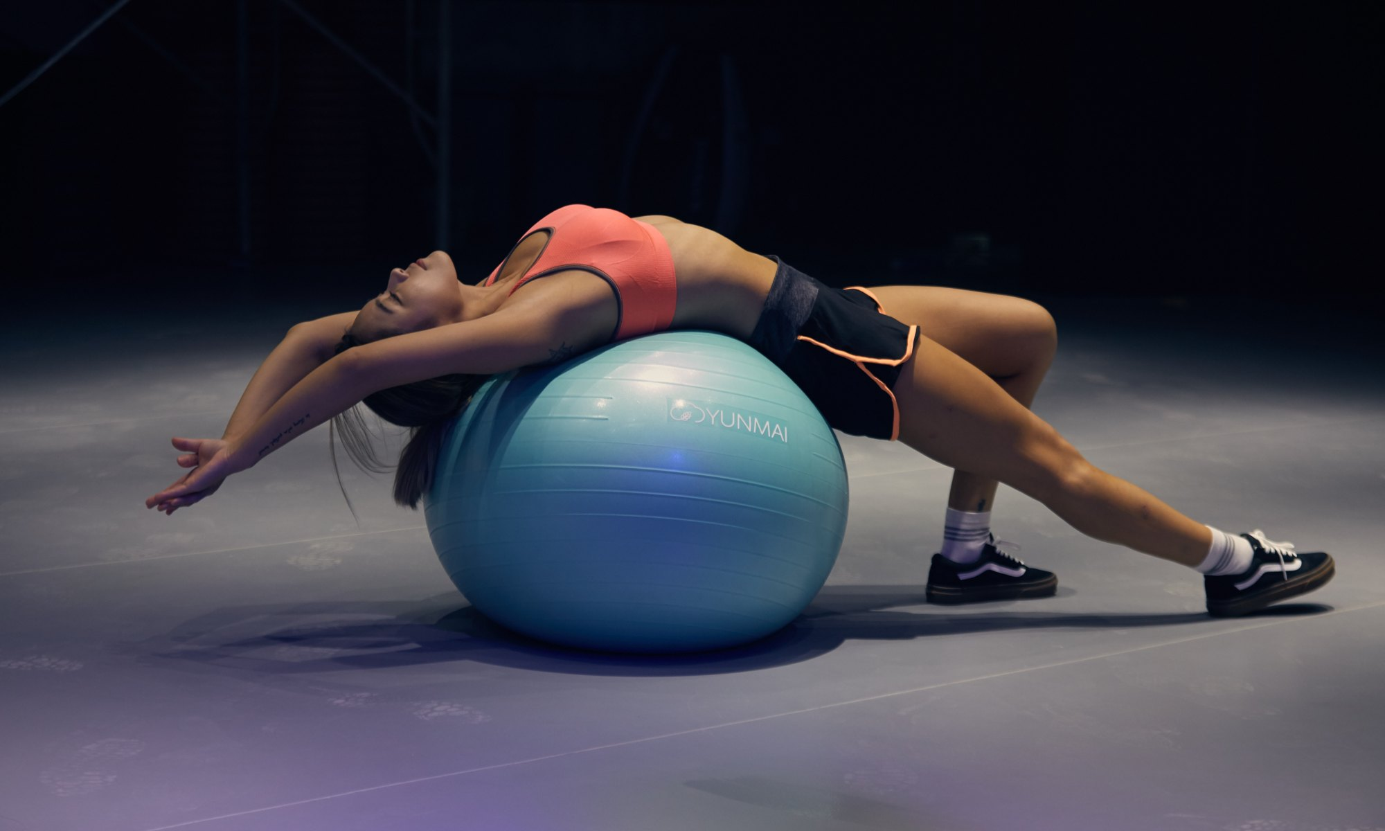 Motivated woman exercising and doing yoga on blue stability ball