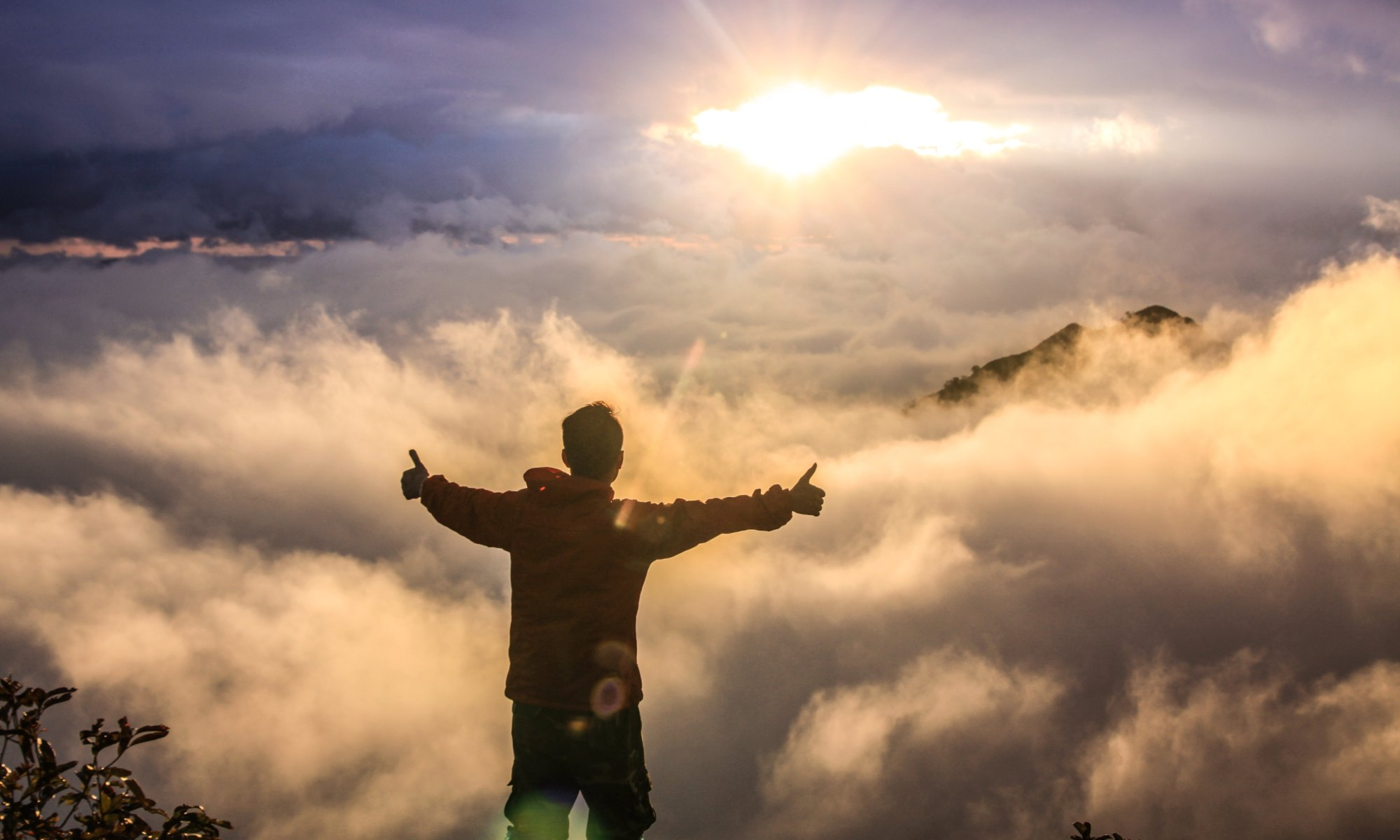 Man who has defeated depression facing clouds during golden hour