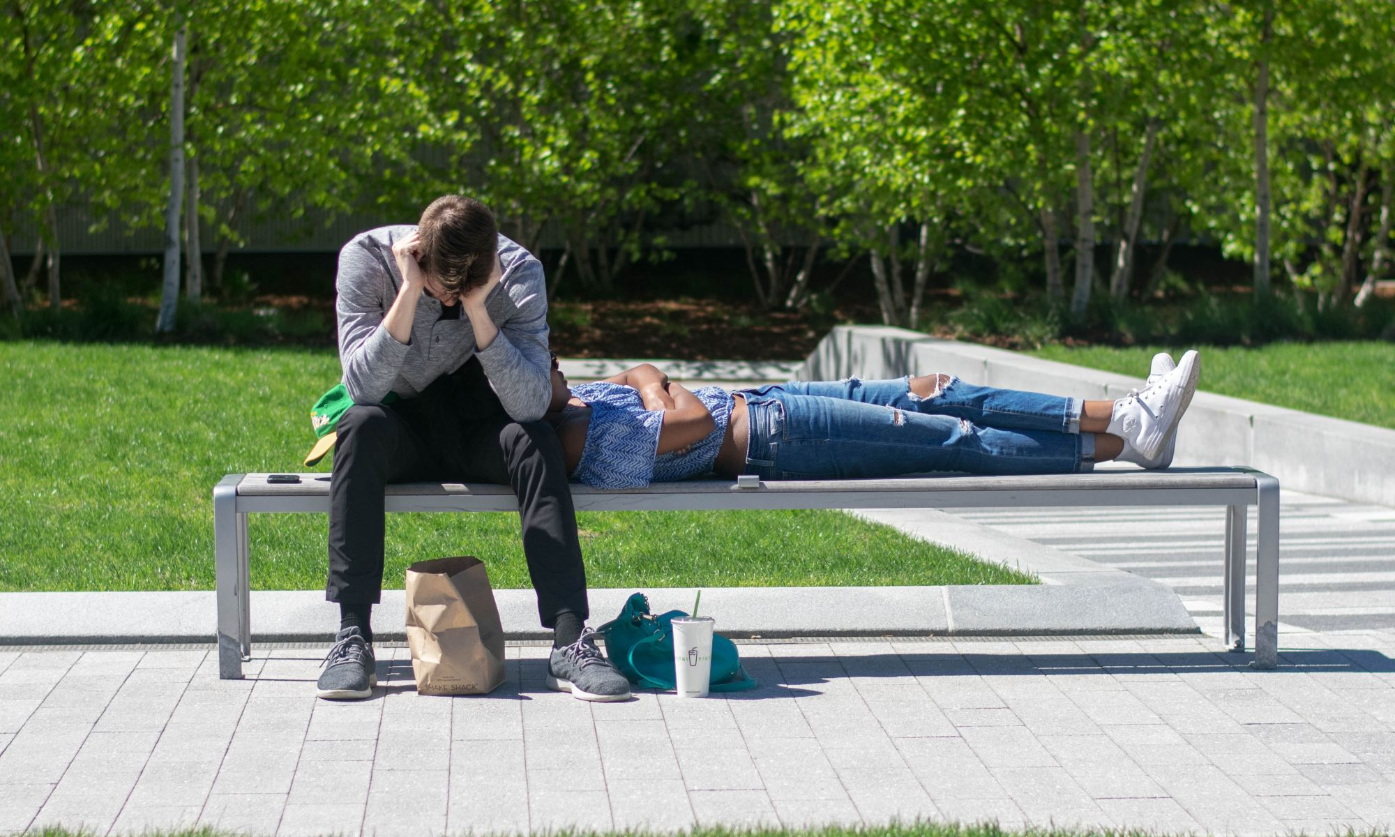 Man suffering from OCD while sitting on white metal bench during daytime