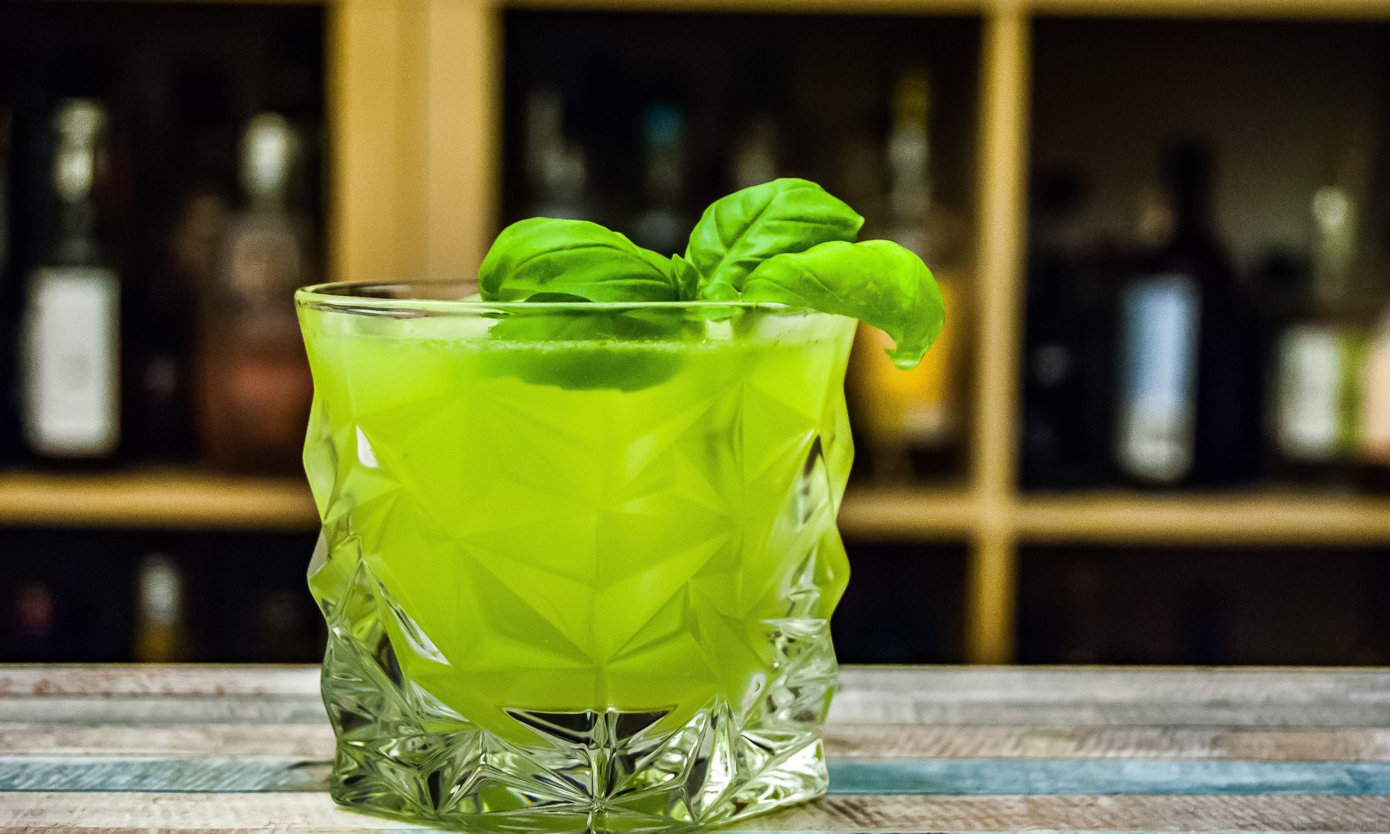Rock glass filled with green alcohol in front of bar