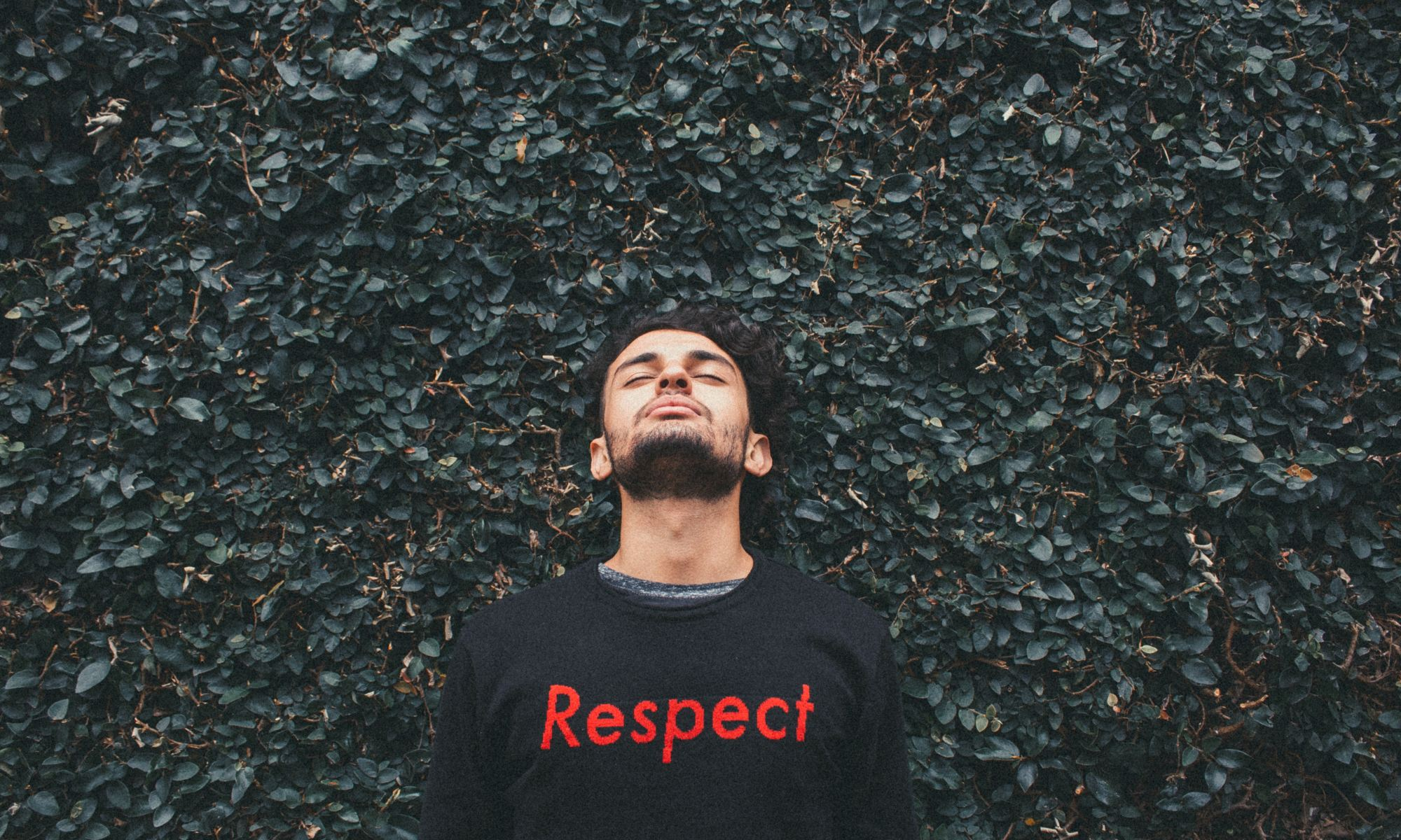 """Man standing behind green leafed plants wearing a black shirt that says """"respect"""""""