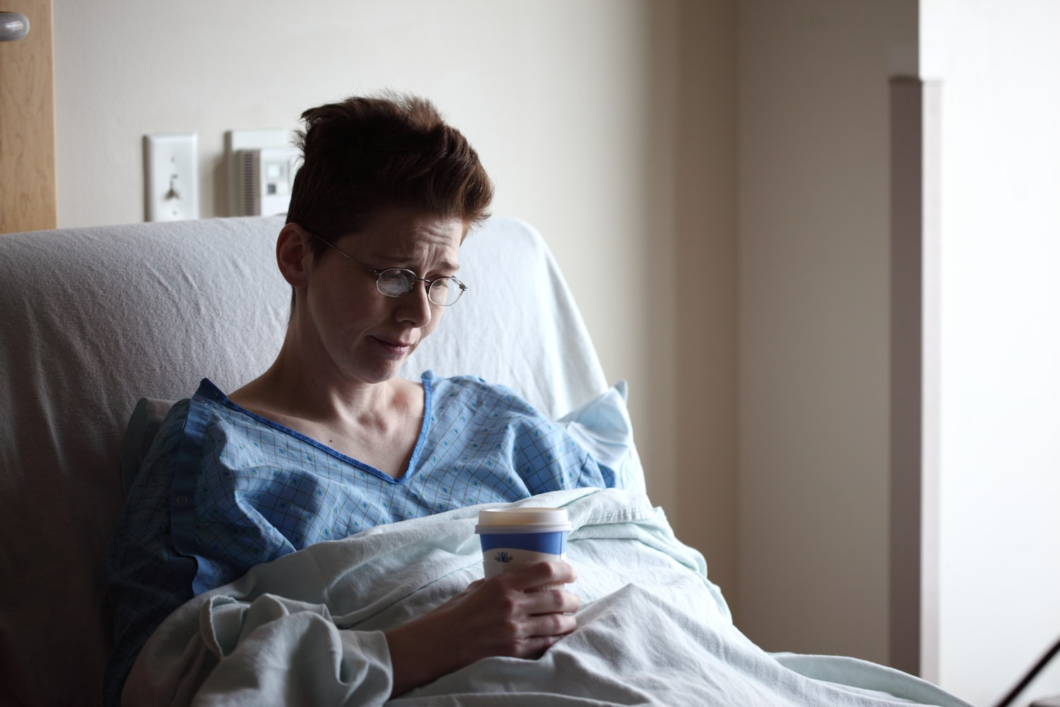 Female psychiatric patient in gown laying on hospital bed