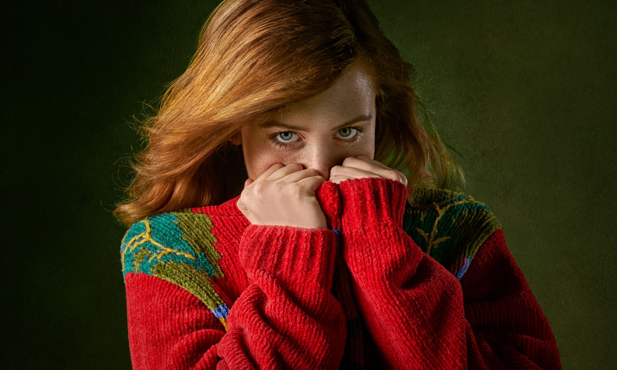 Shy redheaded woman covering up face with red sweater