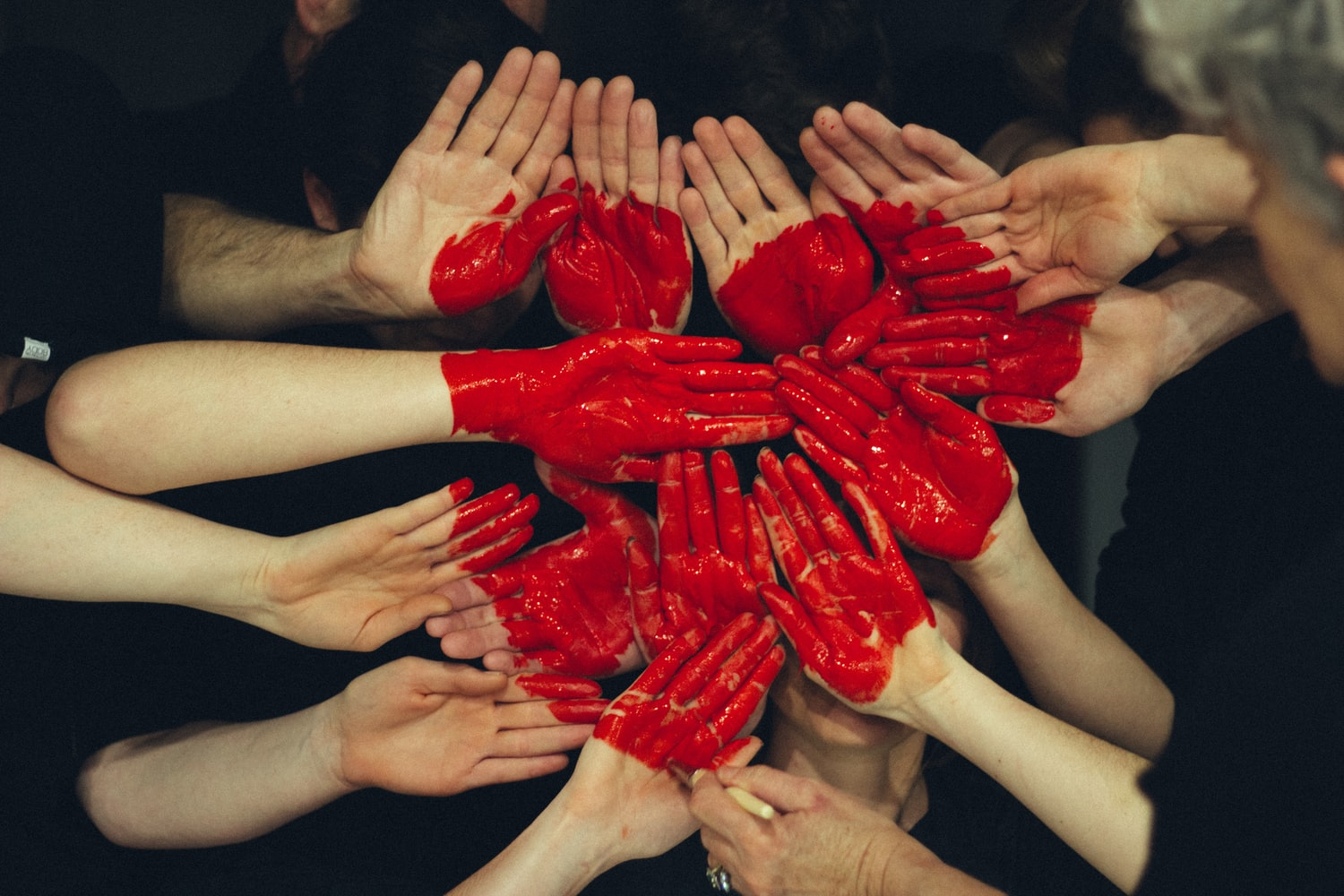 Group of people holding red-painted hands in the shape of a heart