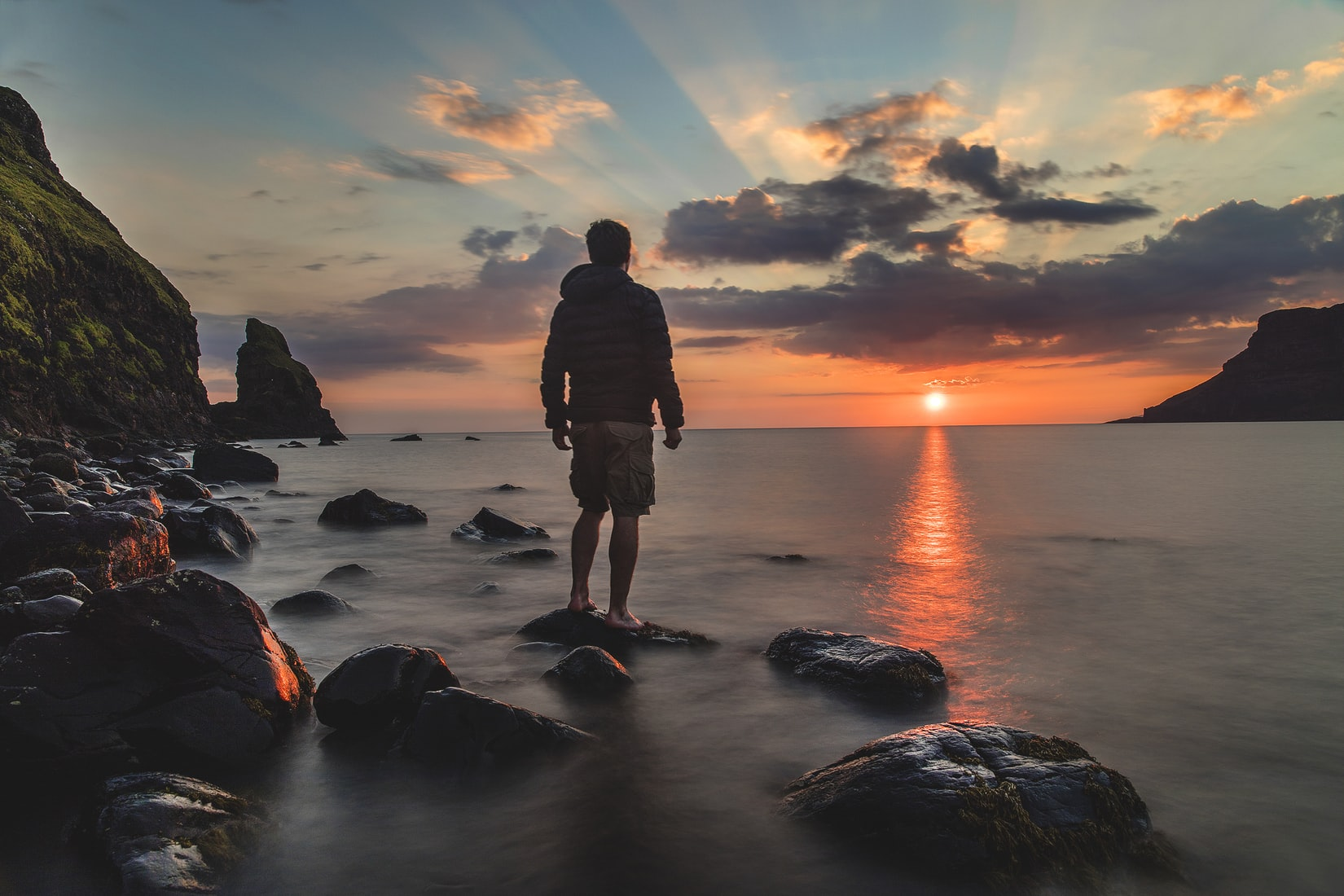 Hopeful man standing on stone in front of body of water looking at sunset