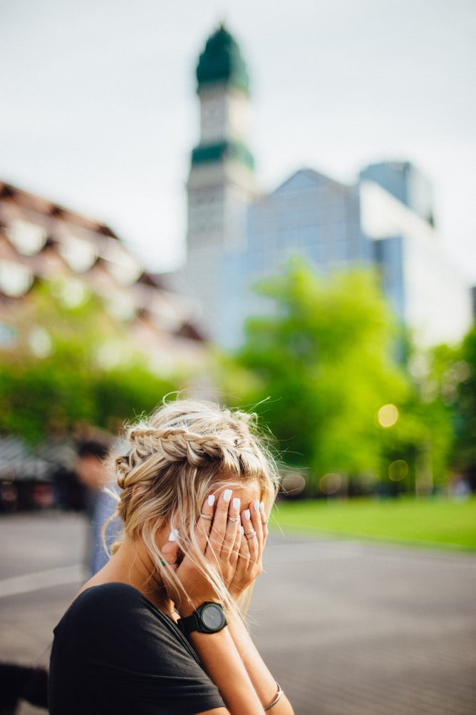 Young blonde woman having a bad day and covering face with hands outdoors