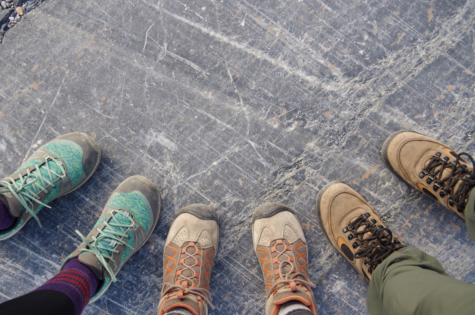 Three persons looking down on their colorful sneakers