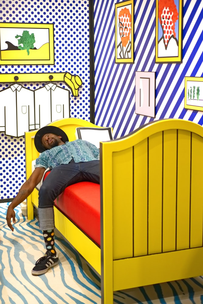 Tired black man lying on yellow bed with red mattress