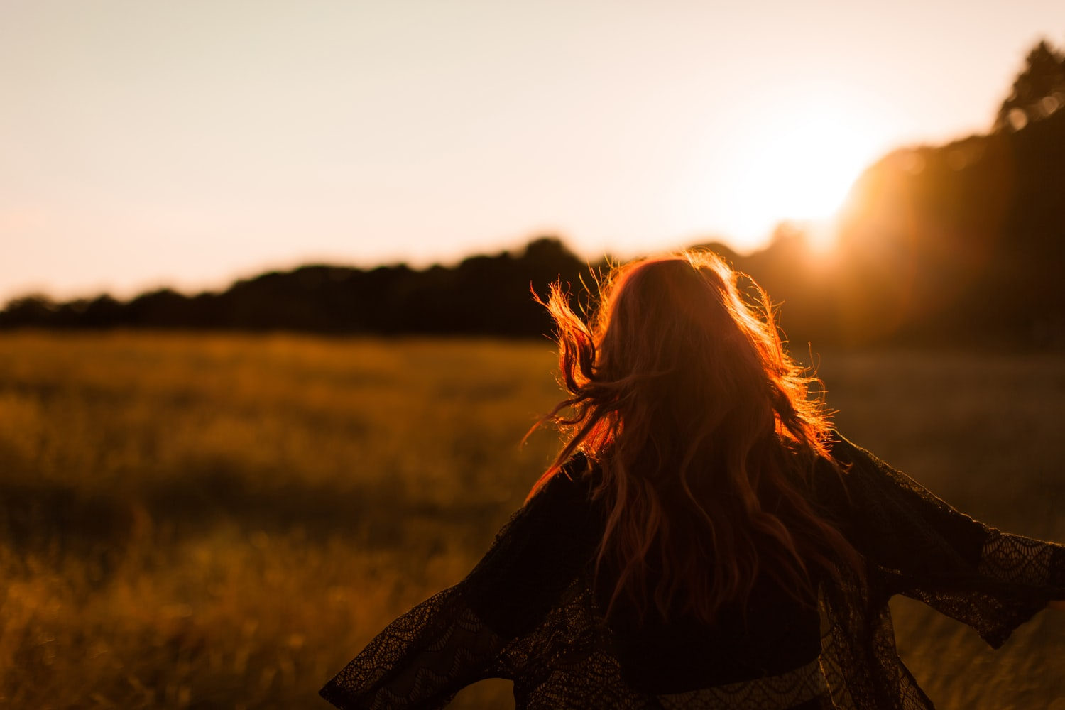 Woman standing on grass field during sunrise