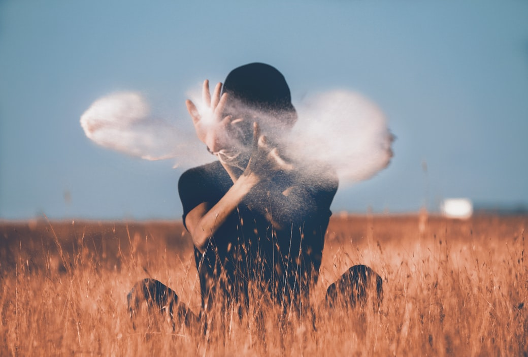 Man redefining himself by sitting on wheat field playing with smoke