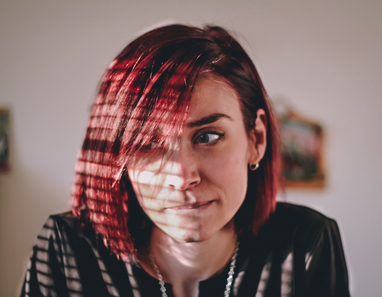 Light from window reflecting on red-haired woman biting lip and ruminating