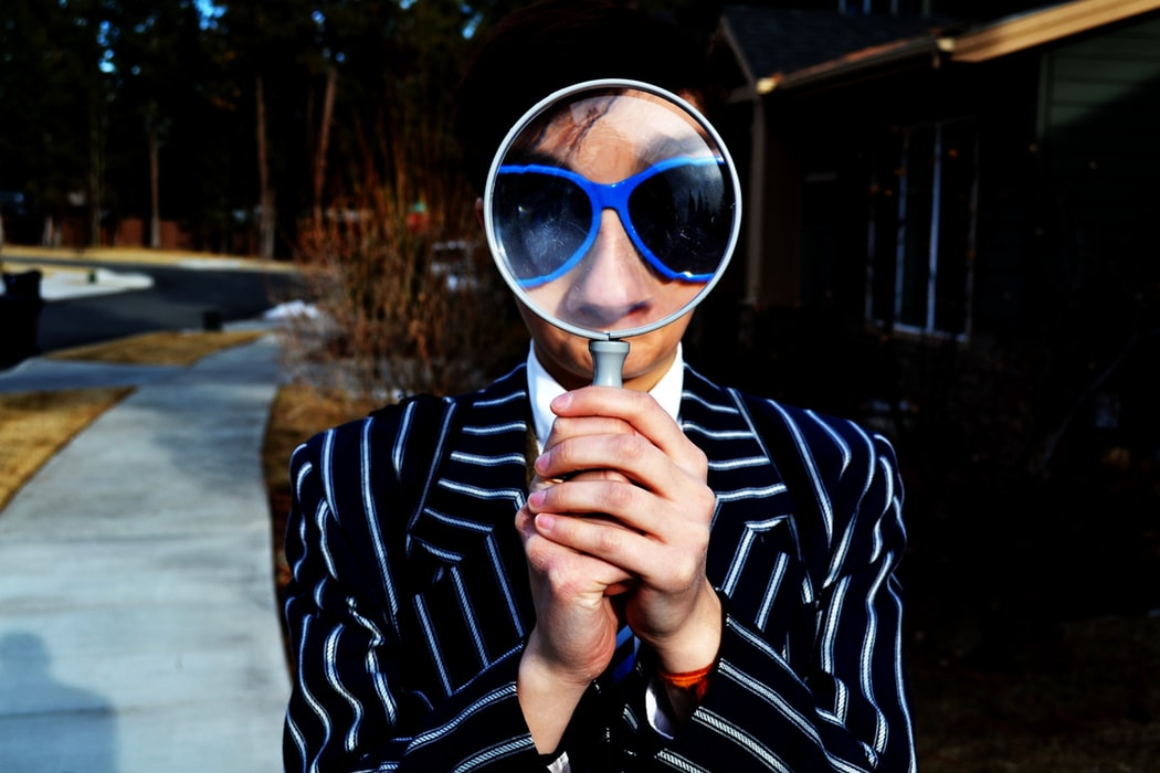 Funny man in suit using magnifying glass to enlarge his blue sunglasses and nose