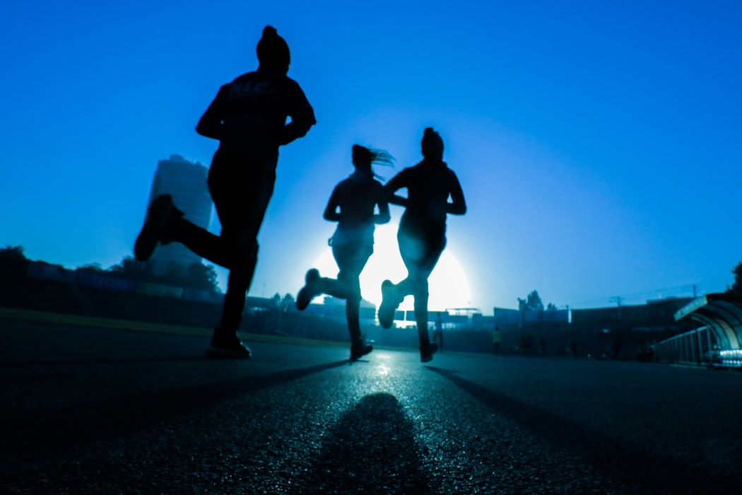 Silhouette of three women running on concrete road outdoors under blue sky