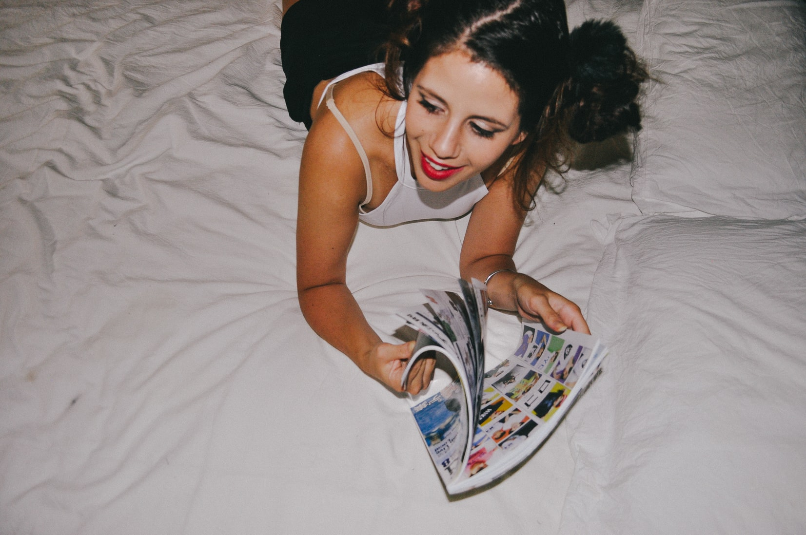 Young brunette woman laughing while on bed reading magazine