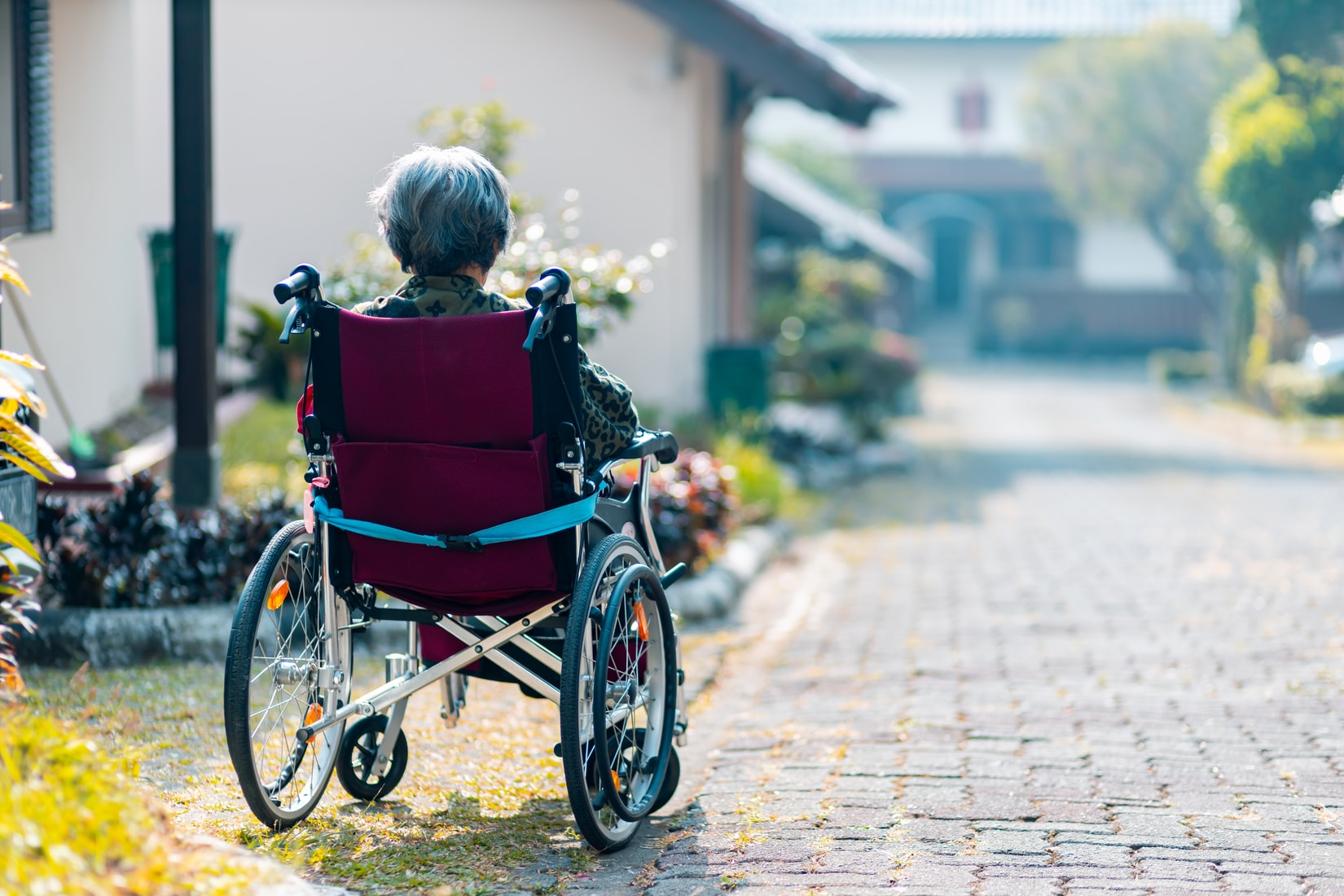 Elderly woman with dementia sitting on wheelchair near houses and stone driveway
