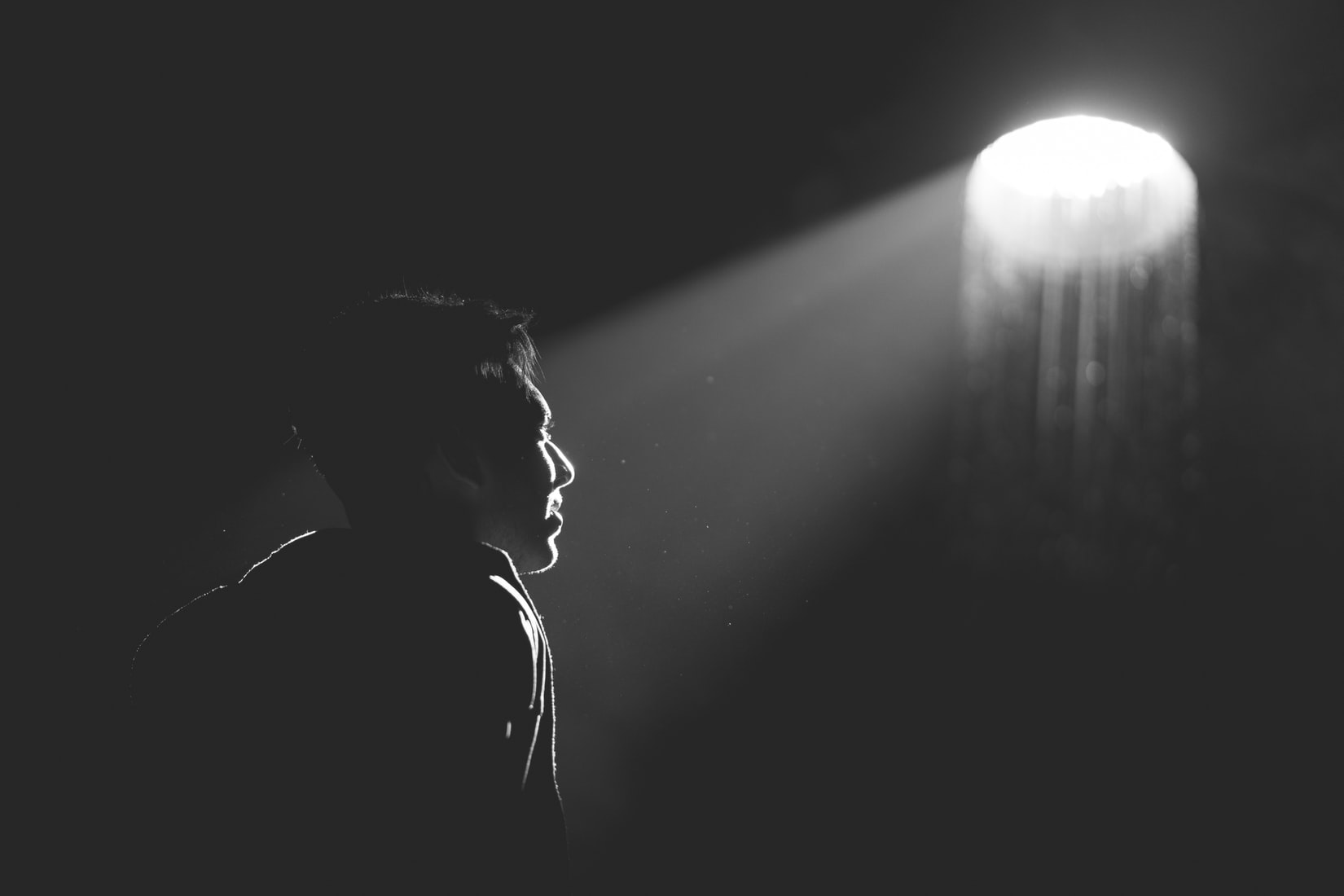Grayscale photography of man looking at incoming light from a hole