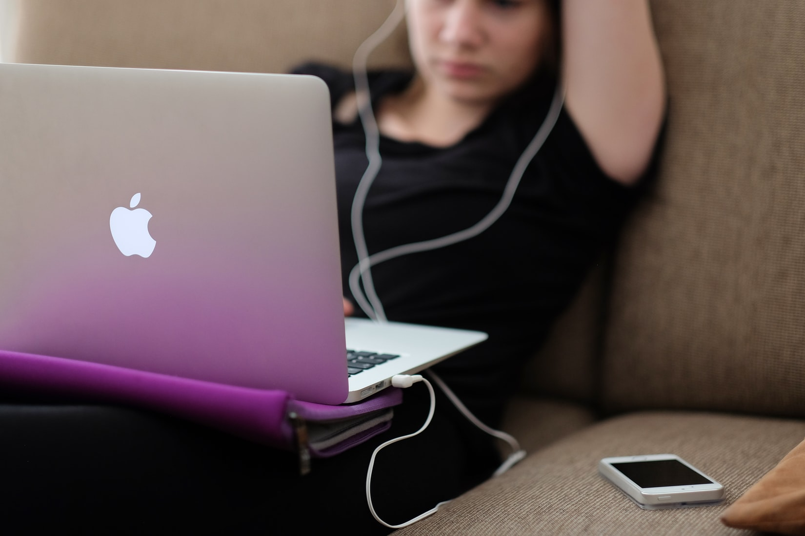 Young girl sitting on sofa and checking social media on MacBook air with headphones on