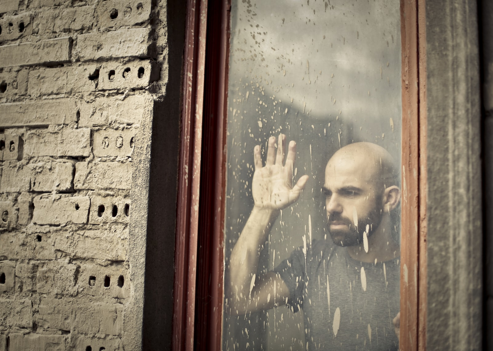 Worried bald man leaning and staring out of window
