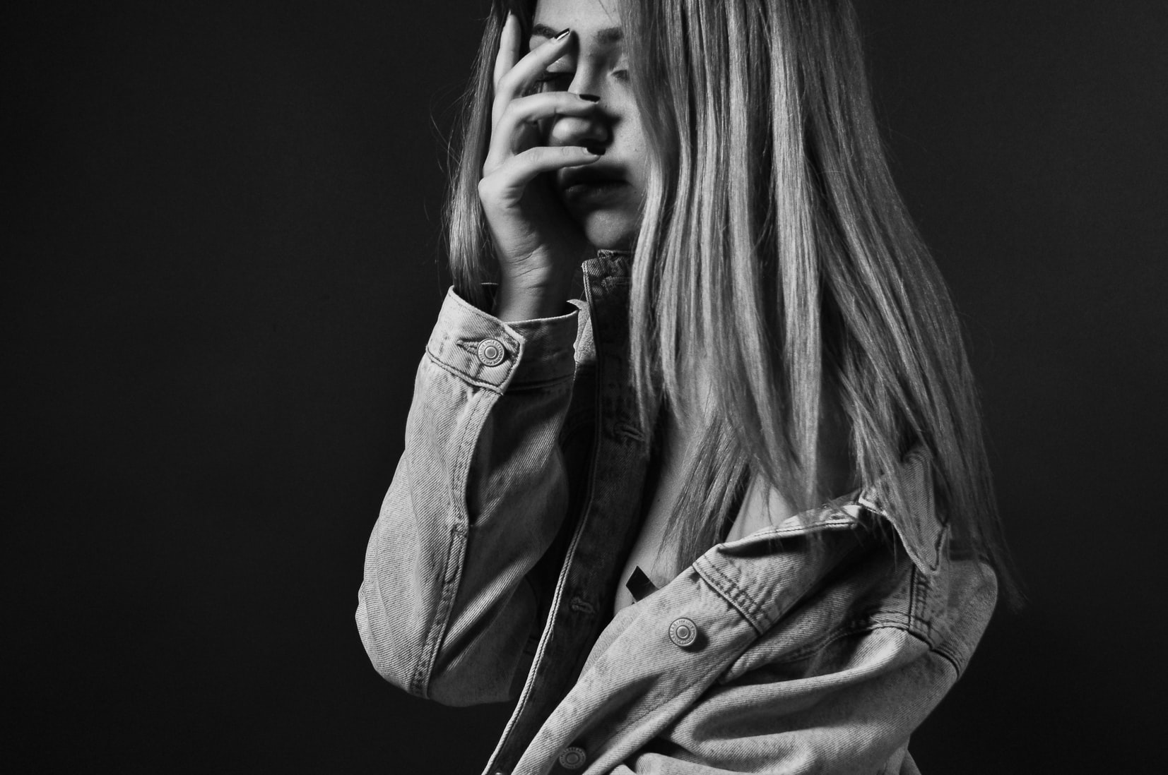 Young girl with depression covering her face with palm