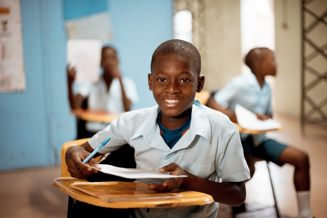 Black boys dressed in blue polos holding paper in class while seated at desks