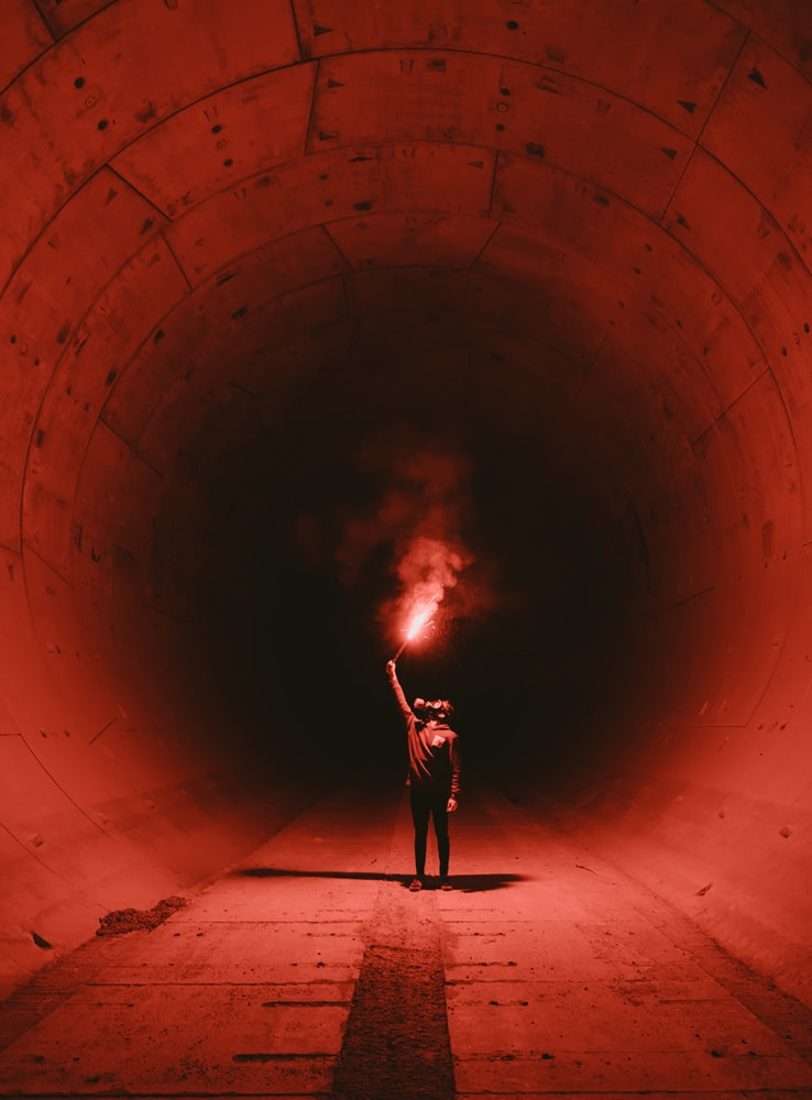 Suicidal man wearing gas mask and holding torch inside dark tunnel