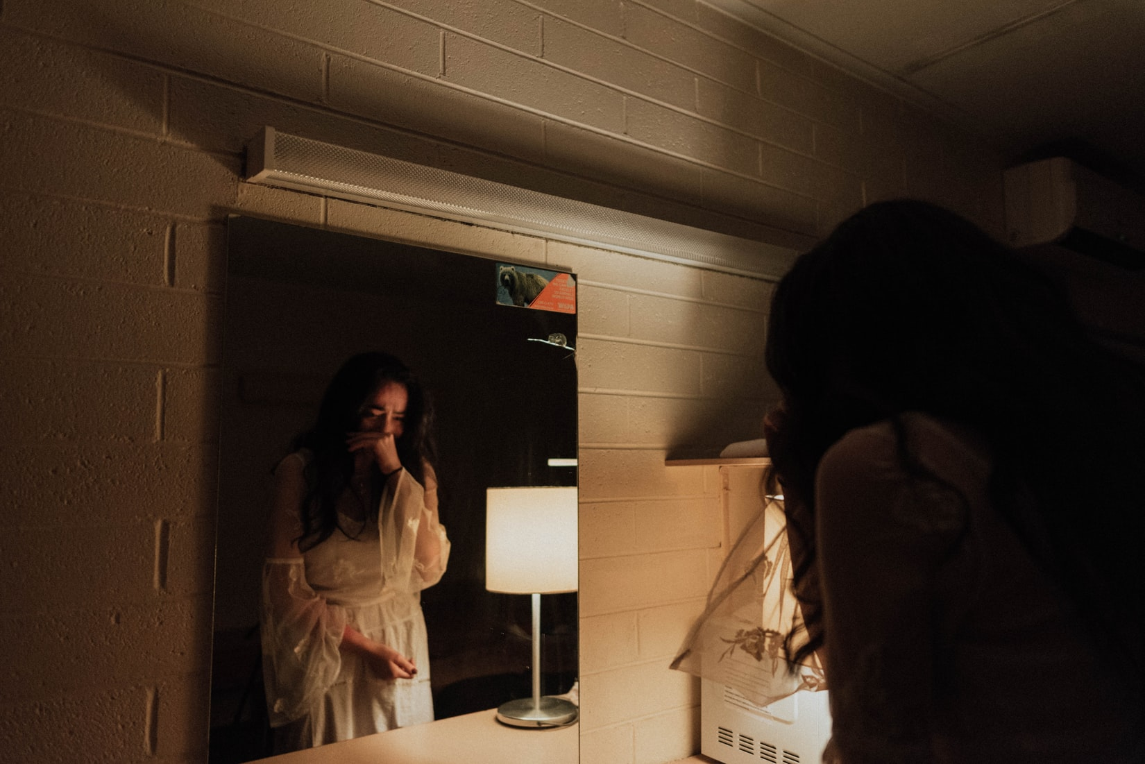 Brunette woman in white robe crying in front of mirror