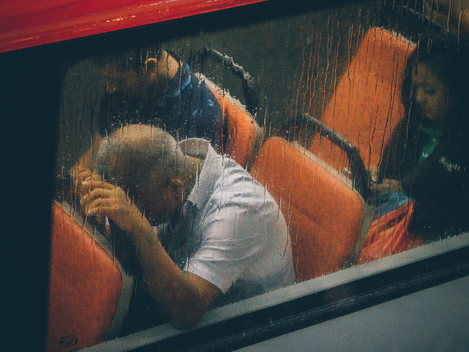 Stressed man sitting on orange chair in bus with head on chair