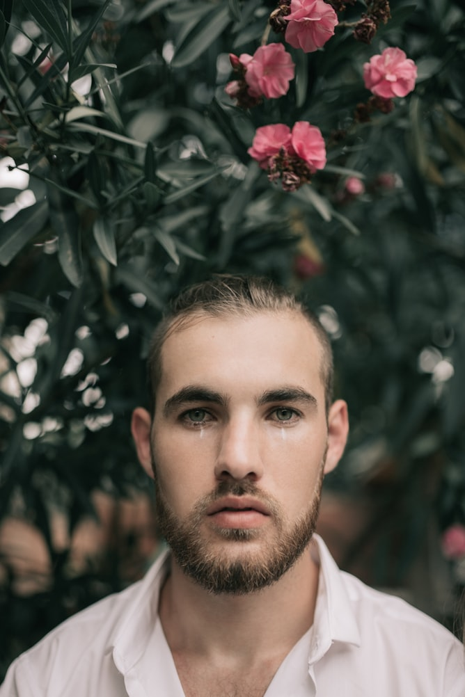 Man with brown beard crying in front of pink flowers