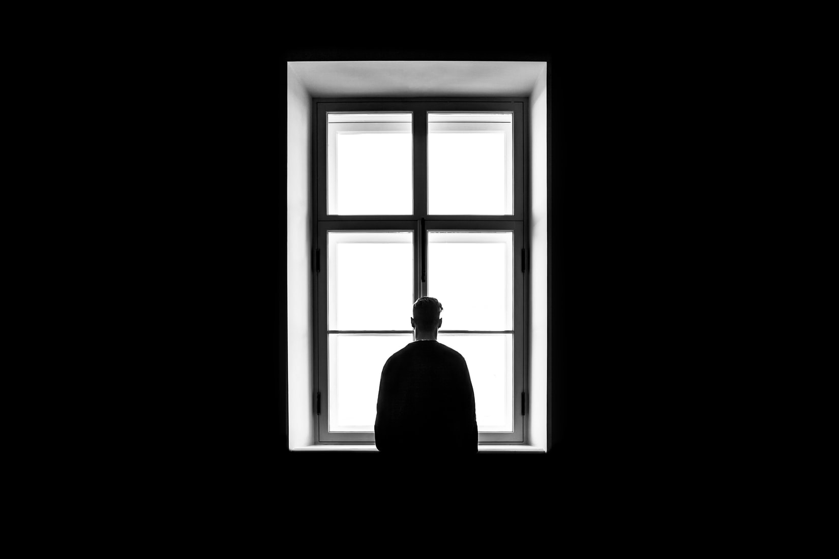 Depressed man standing in front of large window