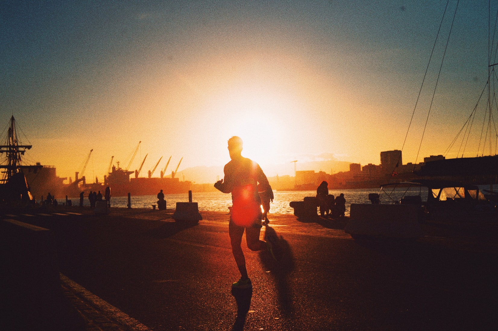 Silhouette of man jogging on the street during sunset near body of water