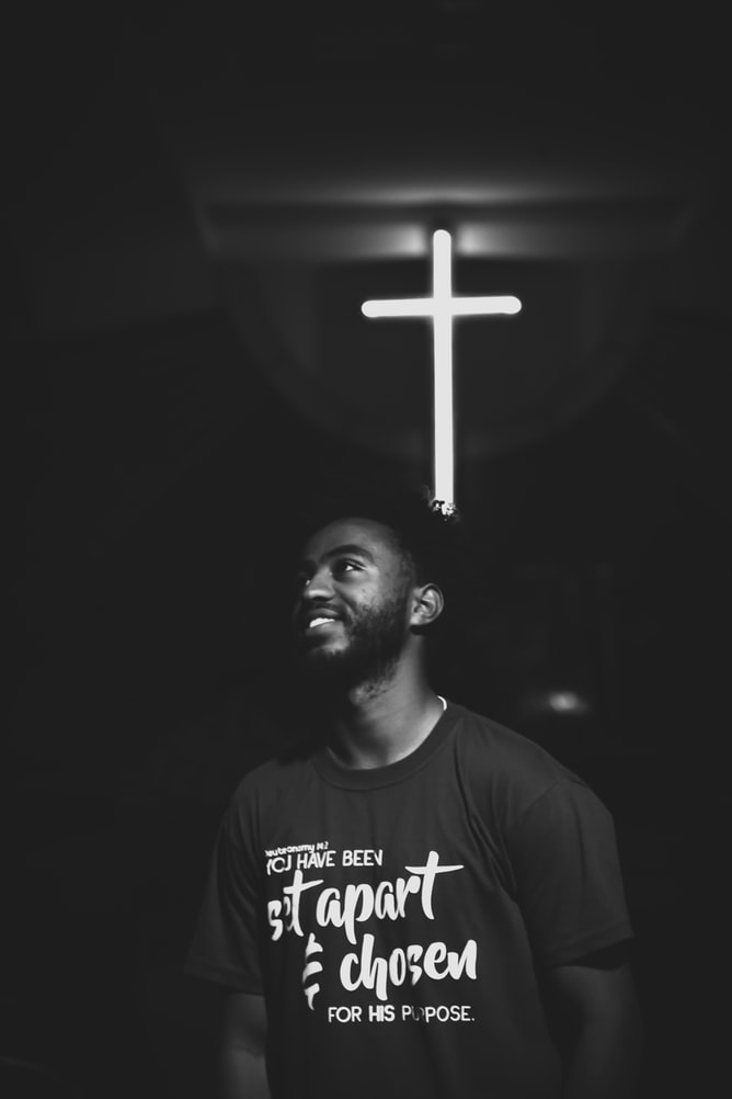 Grayscale photography of black man standing in front of cross smiling