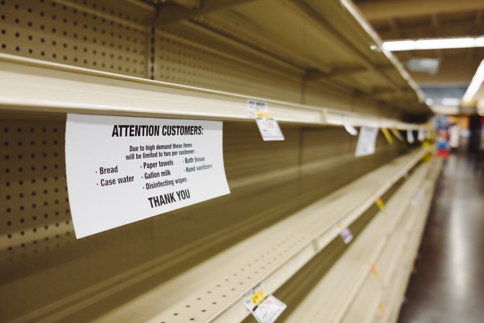 Empty store shelve with white sign warning customers