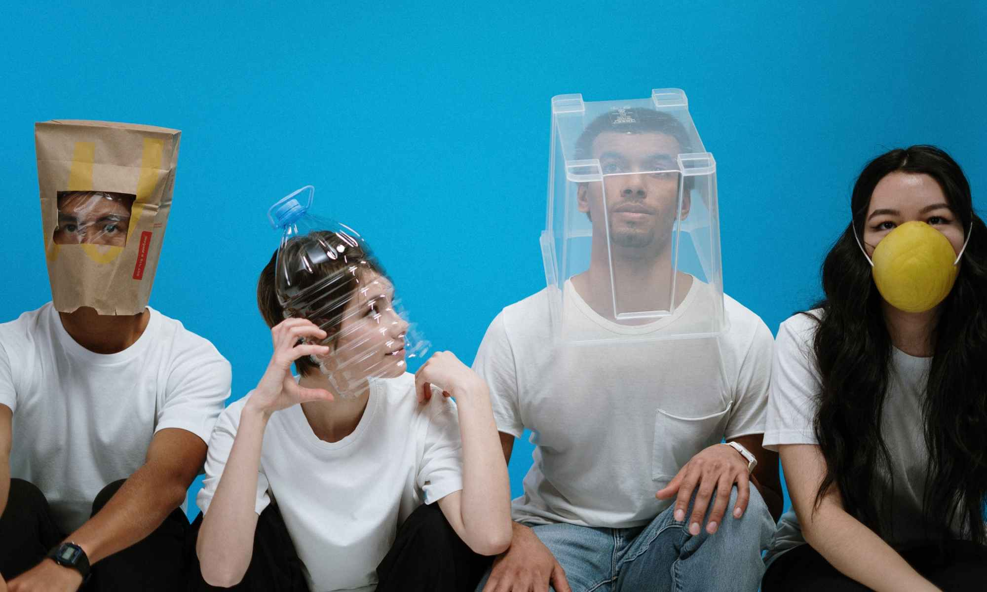 Four young people wearing masks and containers on head