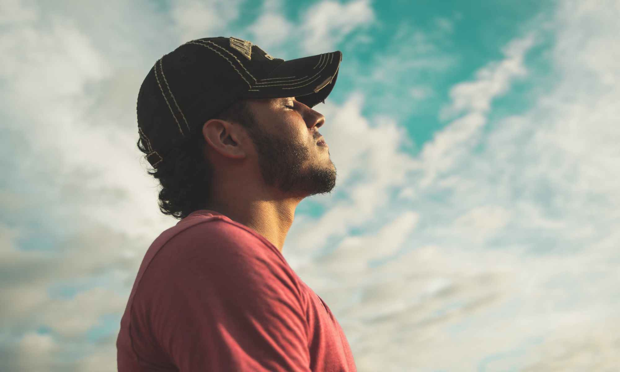 Young man wearing black hat and red shirt with eyes closed under cloudy sky