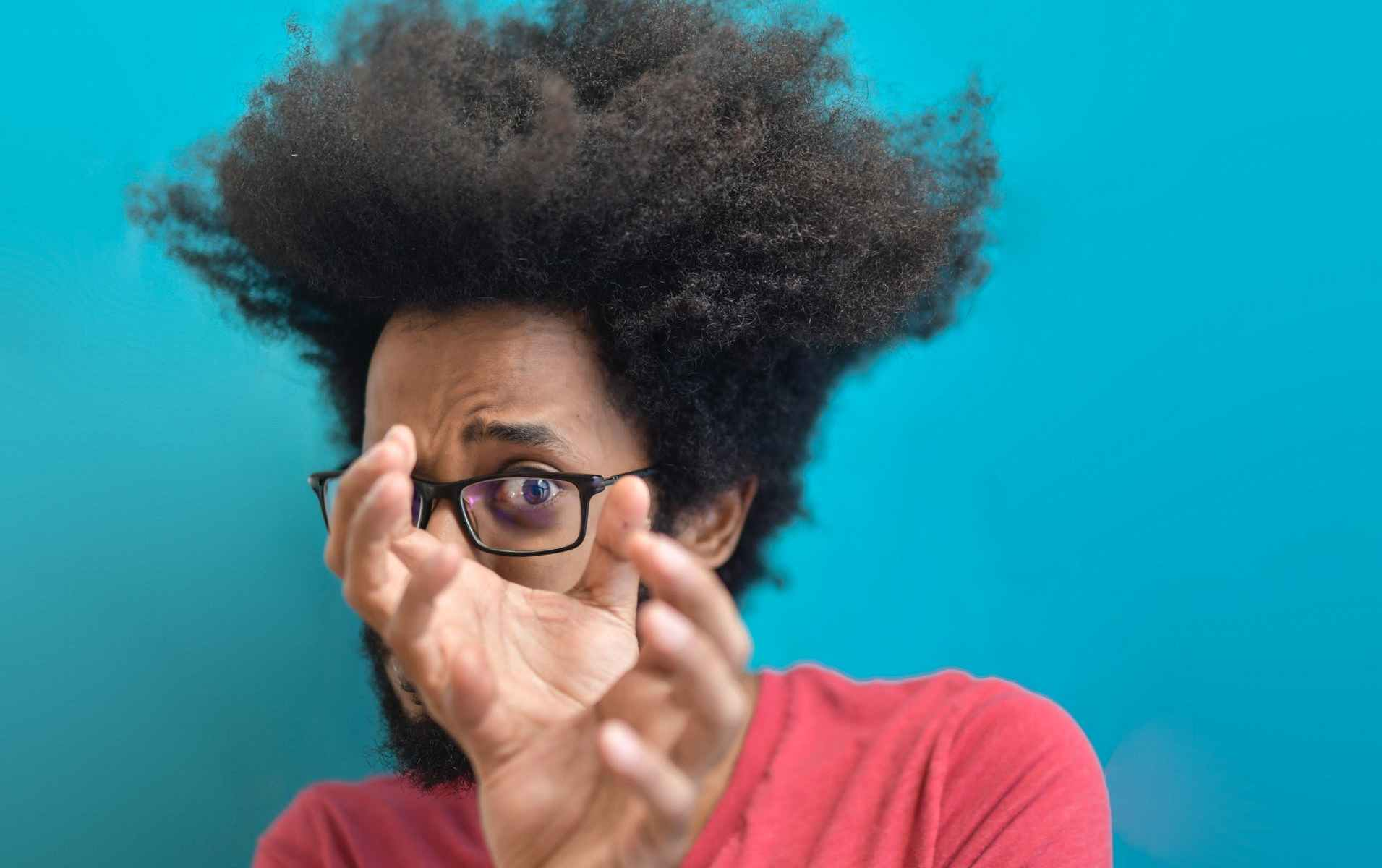 Black man with afro and glasses holding hands in front of left eye