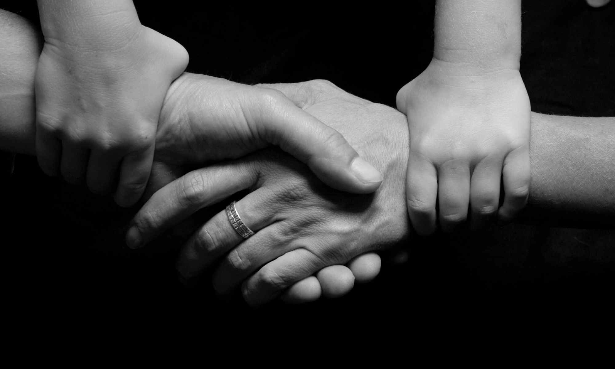 Black and white photography of two adult hands shaking with two child hands holding adult arms