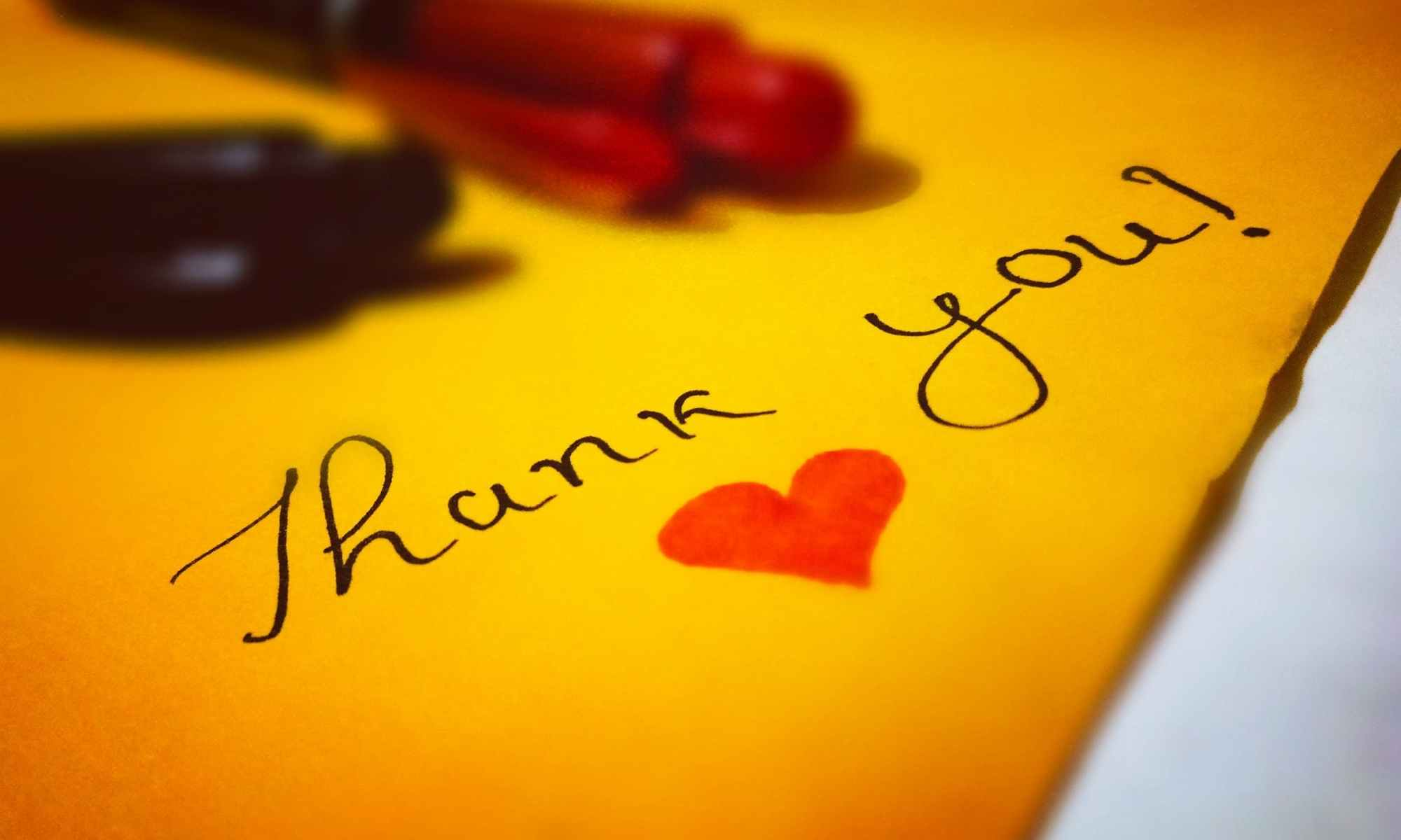 Thank you! heart text written on yellow paper with pens alongside