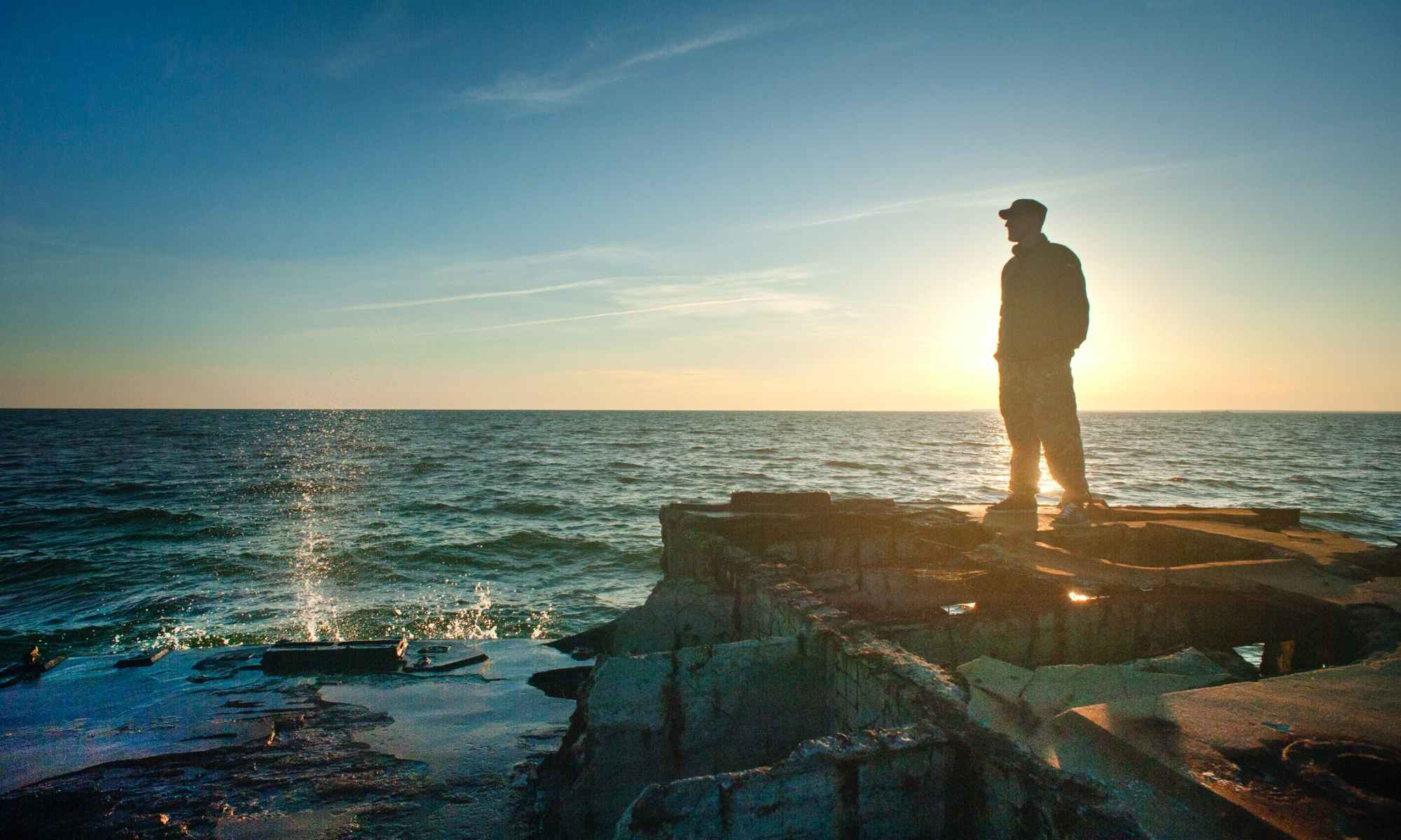 Silhouette photo of man standing on concrete pavement overlooking ocean