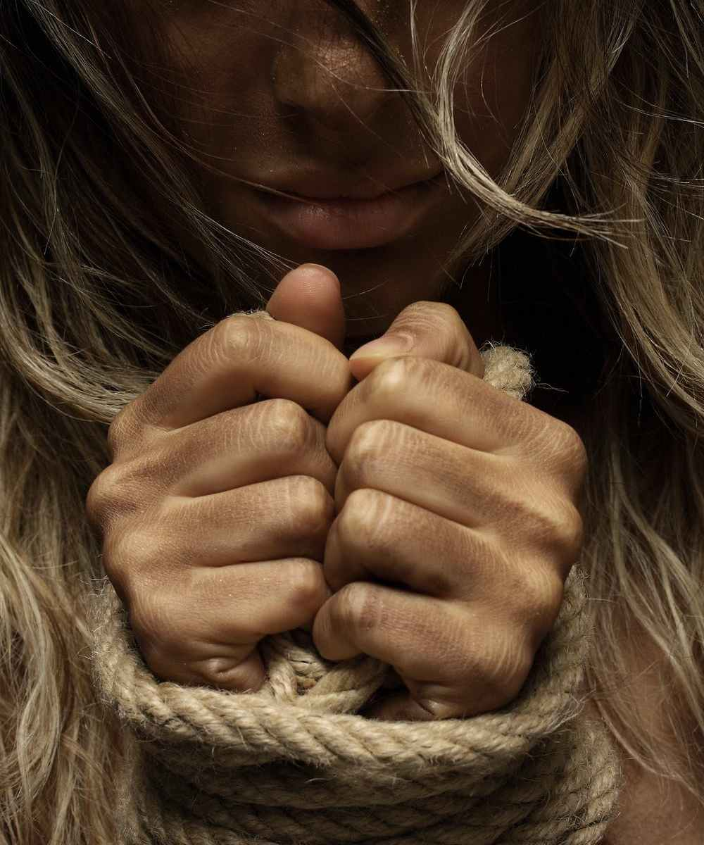 Close-up photo of white blonde woman with hands tied with rope