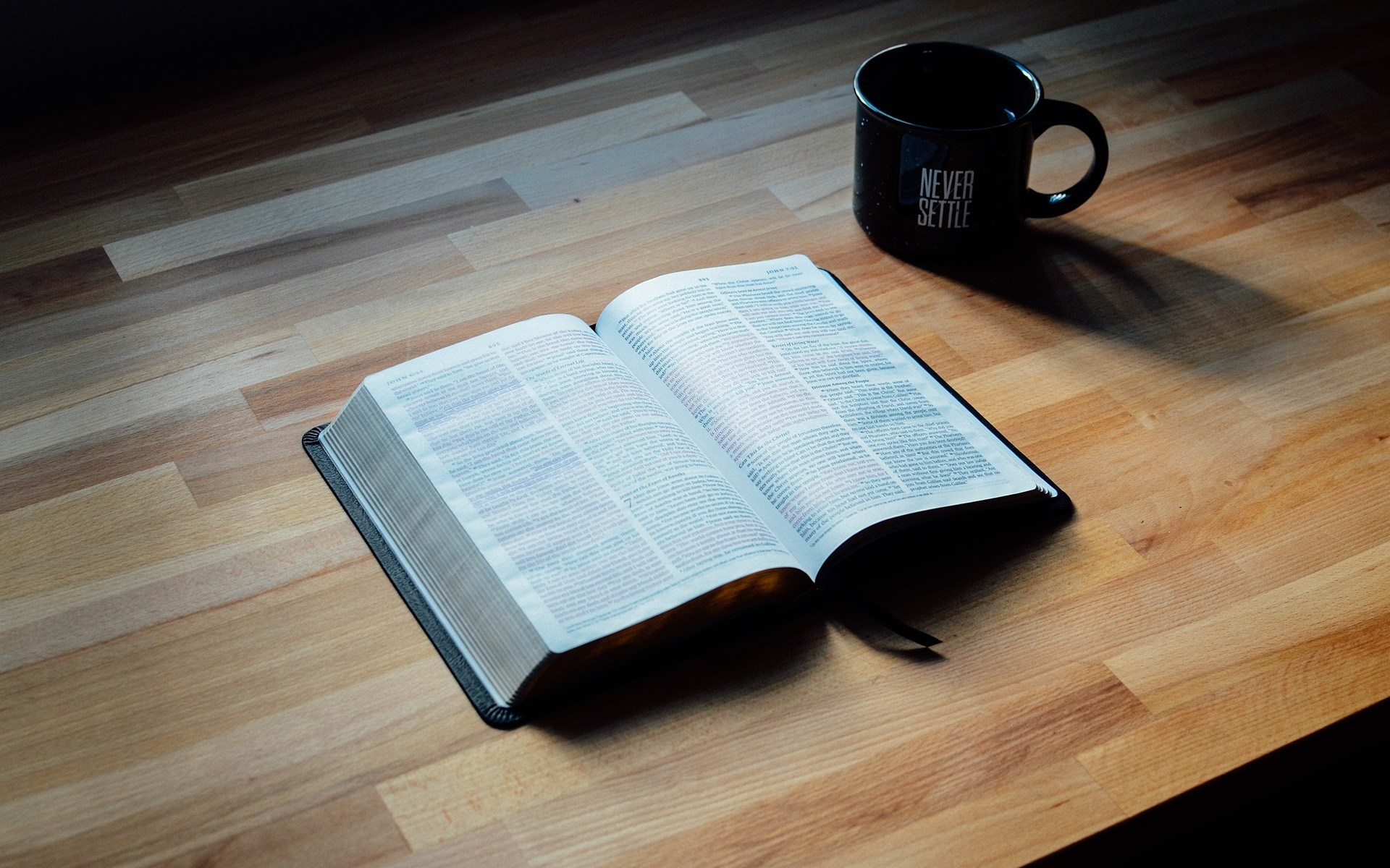 Open book on brown wooden table next to coffee mug