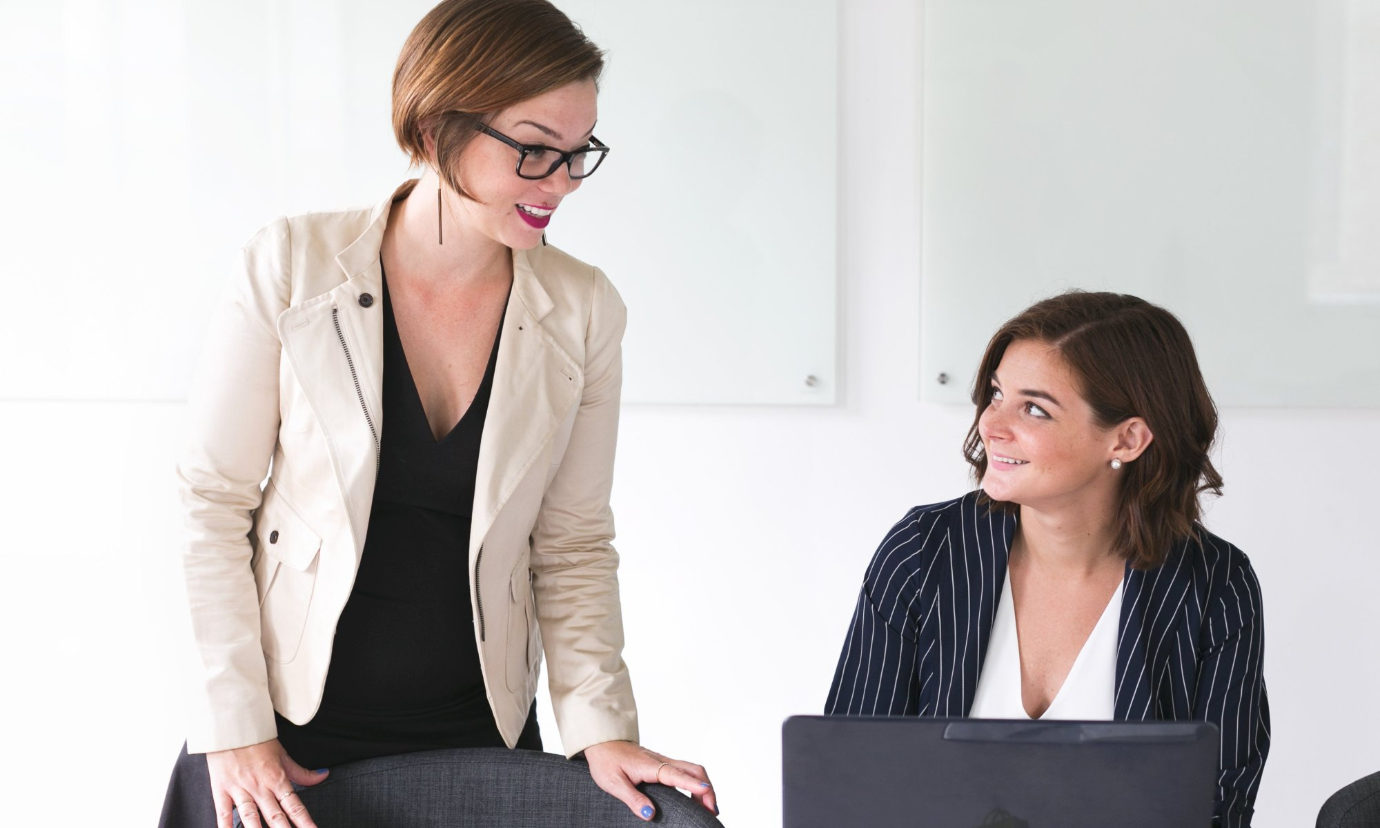 Businesswomen talking and smiling in front of laptop