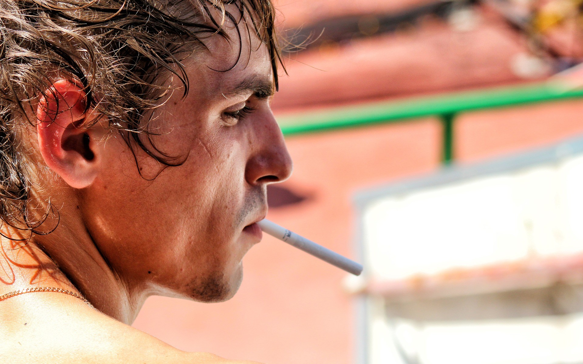 White man with gold chain on neck smoking cigarette