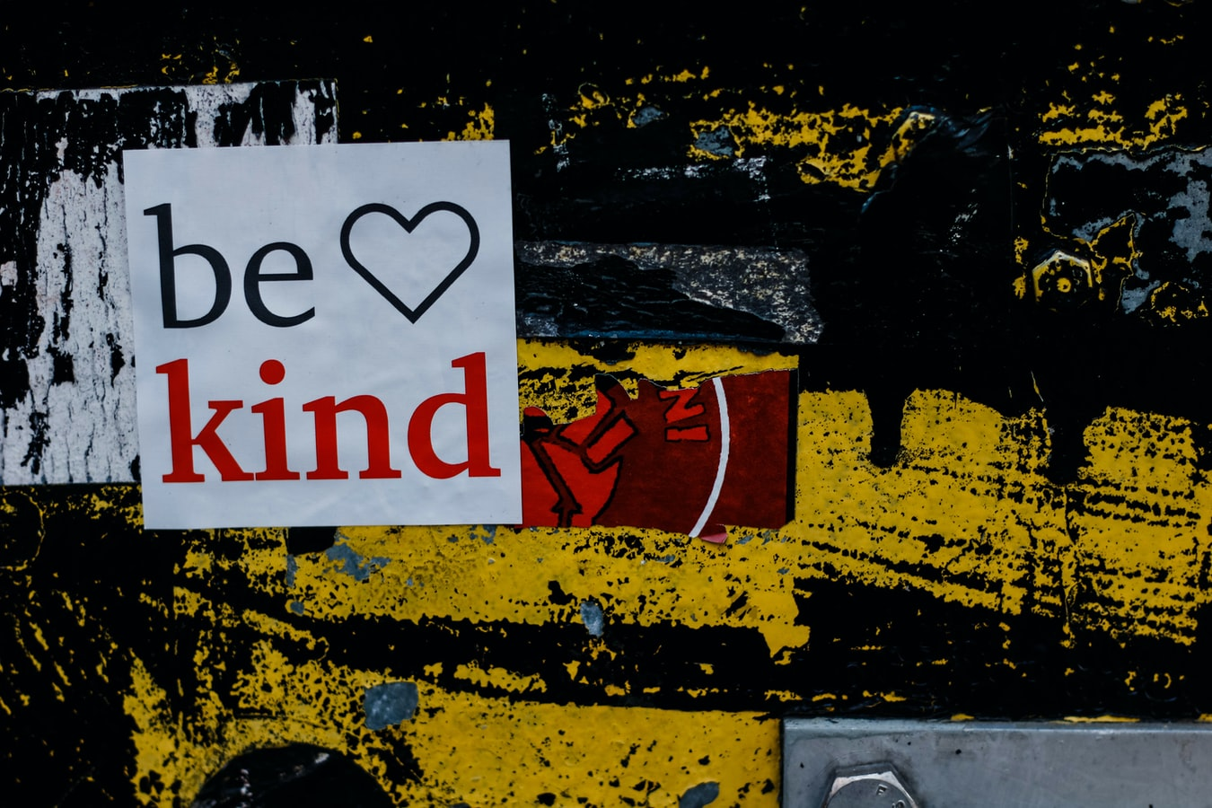 Be kind sign on yellow-painted wall