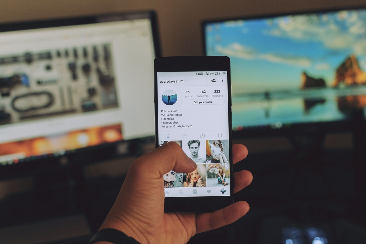 Hand holding phone with Instagram open near two flat computer monitors