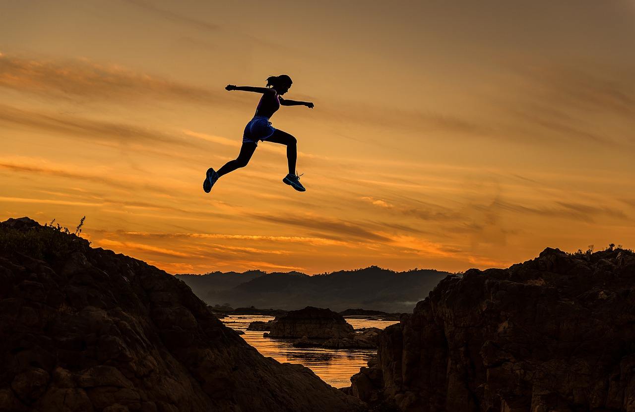 Person leaping from one terrain to another during sunset