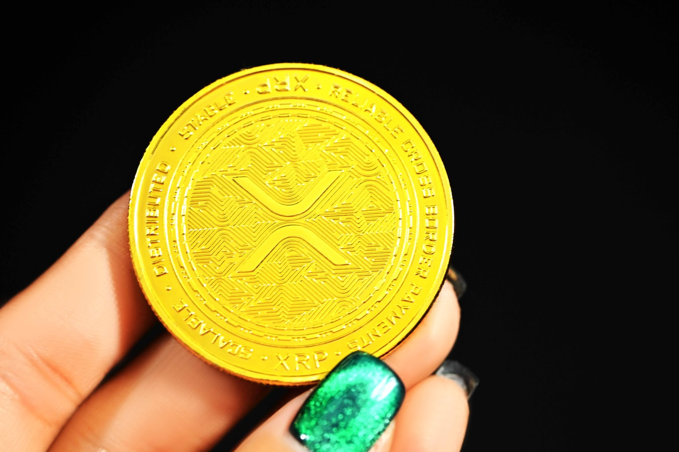 Woman's hand donating yellow XRP the standard token