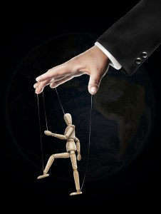Taking advantage of other people - hand holding puppet by strings