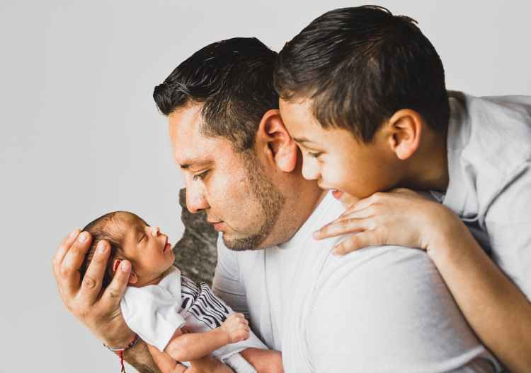 An image of a father with his older looking over his shoulder at the young infant he's holding.